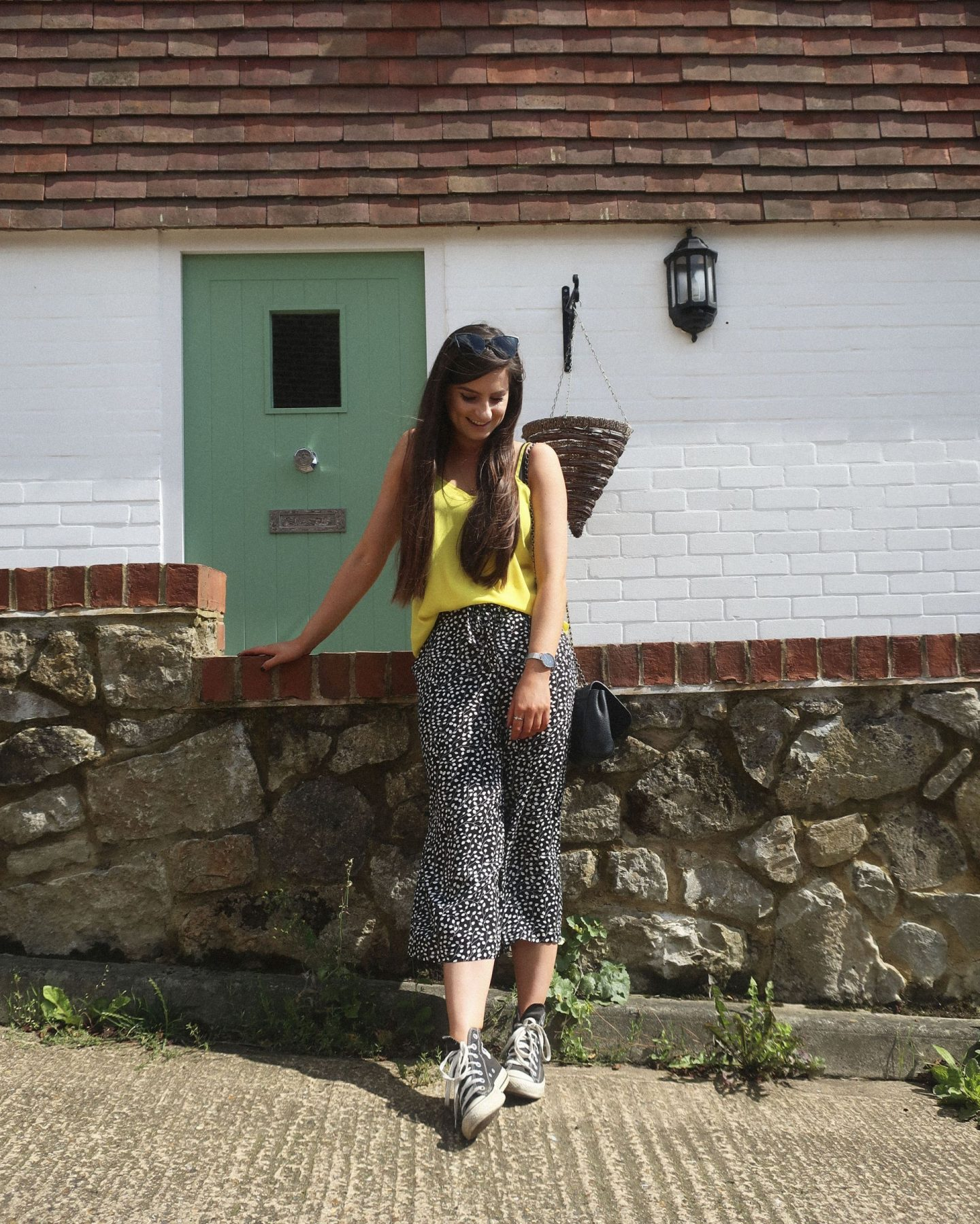 girl wearing black and white polka dot trousers and yellow top with black converse