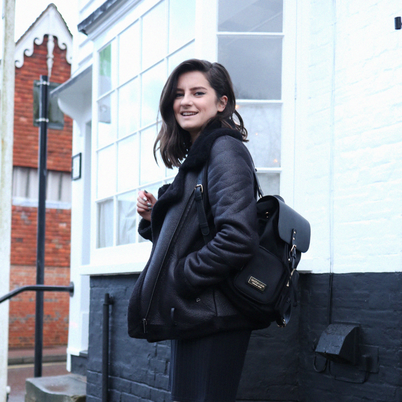 girl wearing all black outfit with gaston luga bag