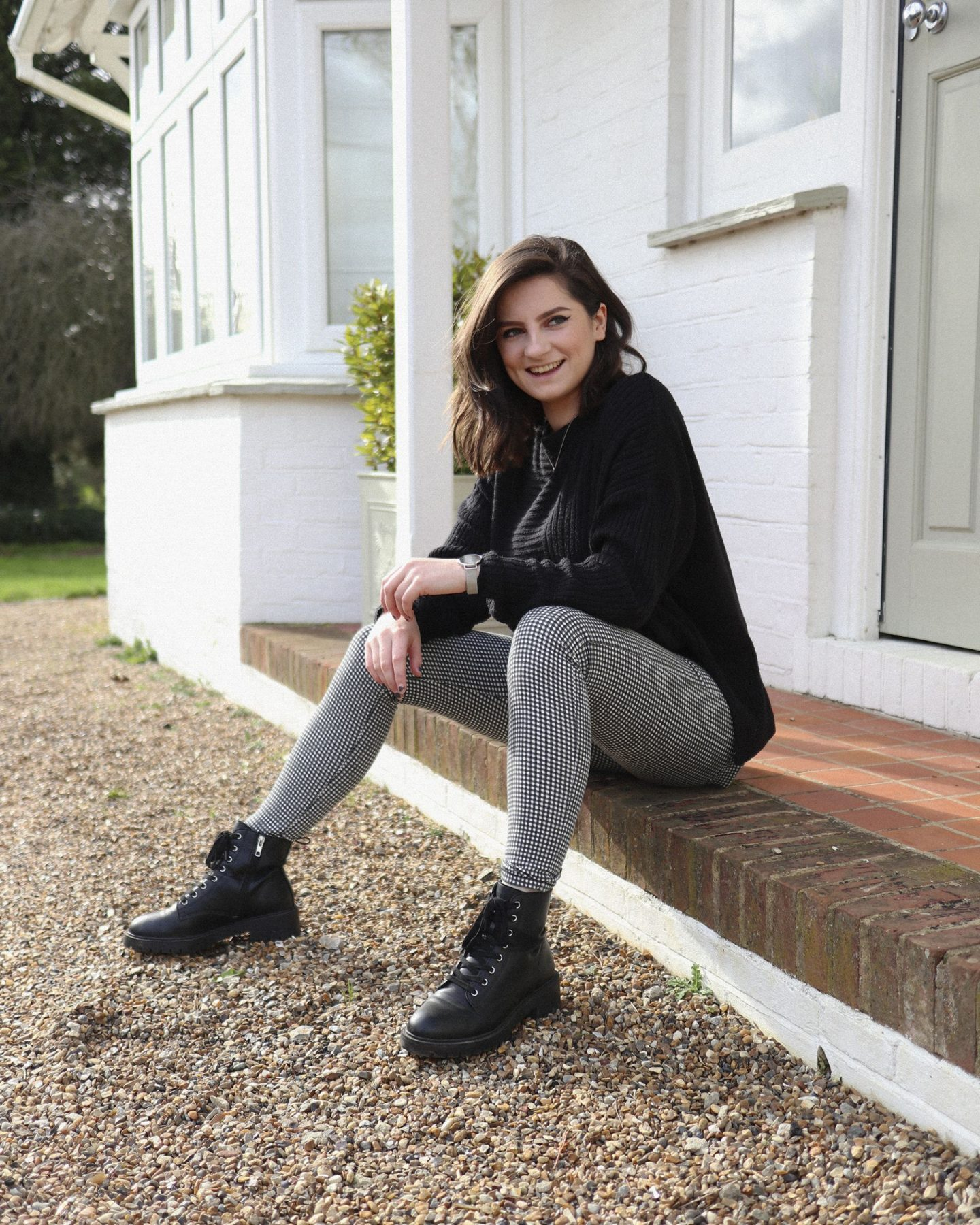 girl with short brown hair wearing checked trousers and biker boots